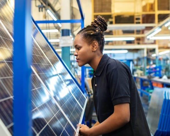 Woman inspecting solar panel