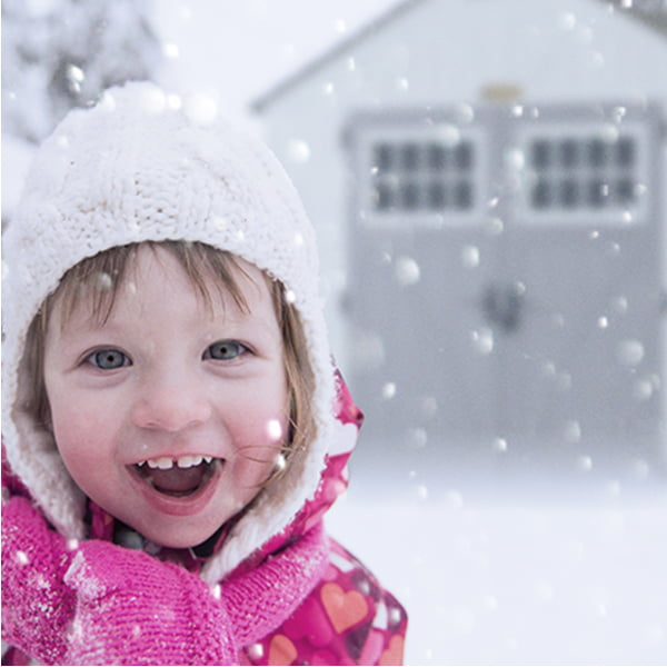 Girl in snow with a shed in the background