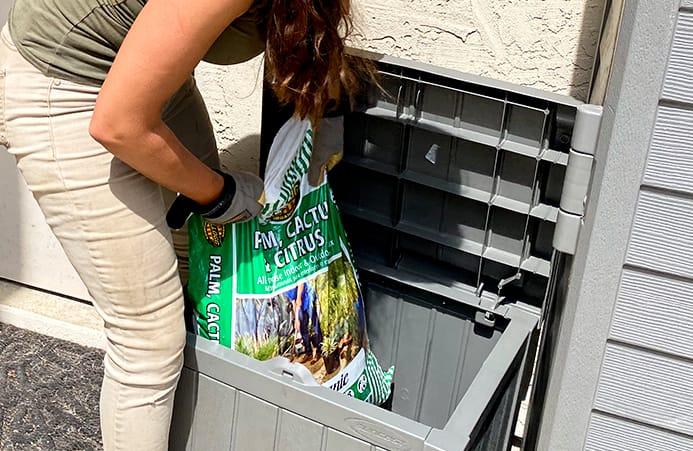 Sara putting bagged soil into a deck box
