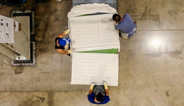 Three workers trimming a door part.